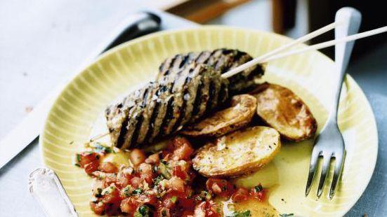 Blötlägg träspetten så att de tål värmen bättre. Blanda ihop samtliga ingredienser till färsen. Rulla och trä på spetten. Blanda tomater, vitlök, salladslök, chili och koriander och smaka av med lime, olivolja, salt, socker och peppar. Låt stå och dra i rumstemperatur minst 30 minuter. Blanda potatis med olivolja och lägg i en ugnsfast form. Rosta i ugn, 220 grader ca 30 minuter. Krydda med salt. Grilla lammspetten runt om tills det är klara, ca 6 minuter. Servera med rostad potatis och…