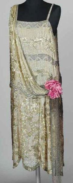 Robe du soir perlée, brodée par Lesage vers 1925. Robe entièrement couverte de paillettes en gélatine et sequins en métal formant des motifs géométriques. Effet d'écharpe drapée sur un côté, fleurs en tissu roses sur la hanche d'où partent de longues franges de perles de verre irisées. Bibl: A rapprocher d'une robe attribuée à Jerôme. GAL 1968-40-67A&B.