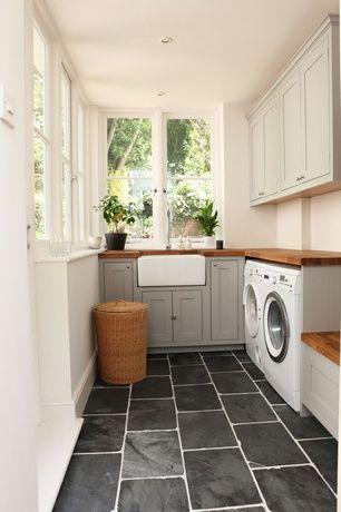 Great Traditional Laundry Room with Built-in bookshelf & slate tile floors.