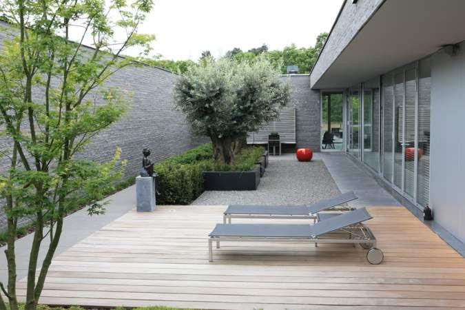 Bij deze woning te Tilburg horen deze twee prachtige tuinen. De moderne patiotuin, die totaal omsloten is, heeft een strakke, ruimtelijkeen cleane uitstraling. Deze ruimte doet dienst als entree van de woning en wordt gebruikt als relax-welness ruimte. De achtertuin is vervolgens groen en weelderig met een perfecte aansluiting met het aangrenzende natuurgebied. Tevens een bijzondere salontafel metwatertafel voor bijvoorbeeld het koelen van de Champagne.