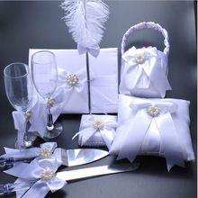 Blanc couleur de mariage décoration anneau de mariage oreiller et panier de fleurs et des verres de Champagne et couteau et…
