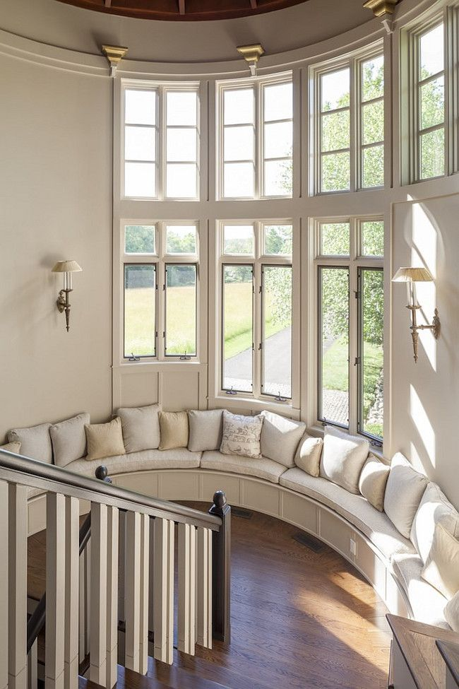 Beautiful staircase landing with beige walls, large windows and a circular window seat with throw pillows | Christie's Real Estate