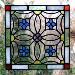 花紋様のステンドグラス ミニパネルです。可愛らしい印象で、リビングやキッチン、ベッドルームなどどんな場所にもなじみます。パネル上部には吊り下げ用の金具が付いていますので、お手持ちのチェーンや紐で吊り下げて飾ることができます。陽のあたる窓際に吊り下げると、ガラスの色が鮮やかに(濃く)浮き上がり、とてもきれいです。お好みで飾る向きを変えていただけます。作品は自立しませんが、壁に立てかけたりお手持ちの皿立てに立てかけて飾ることも可能です。その場合は倒れて割れないよう布などを敷くことをお勧めします。 リビングボードの上や、飾り小窓、出窓などに飾っても素敵です。DIYが得意な方は、ドアや壁にはめこんたり額に入れて飾ってみてはいかがでしょうか。大きさ:たて約15cm×よこ約15cm×厚さ約3mm 重さ:約200g 素材:ガラス、鉛●ご購入の前に必ずご確認ください。作品はすべてハンドメイドの一点ものです。 ガラス作品のため、光のあたり具合によって色の見え方や透明感が違ってきます。…
