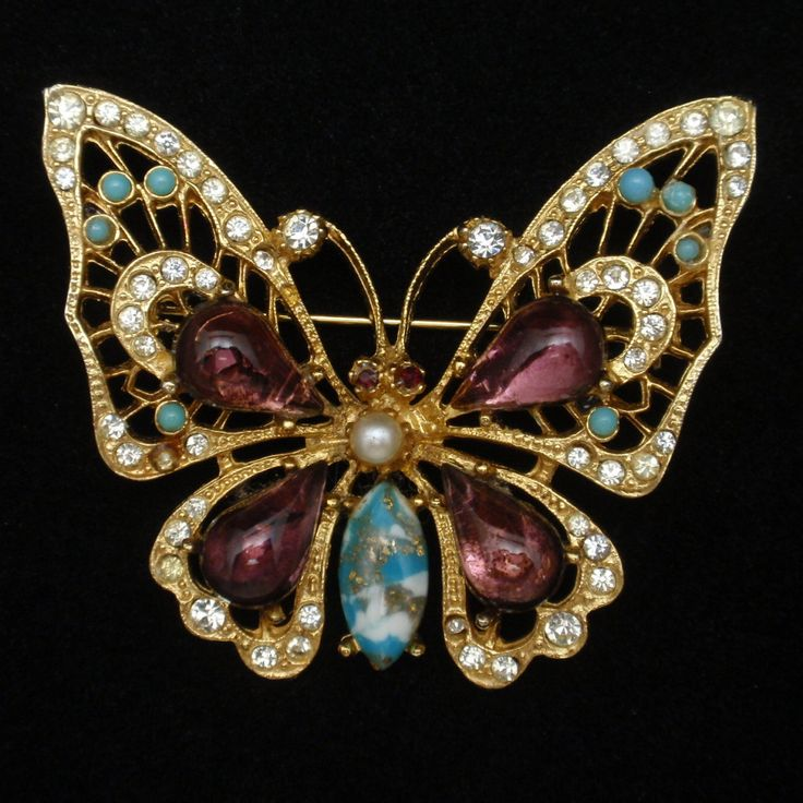 Gold tone butterfly pin set with large purple and art glass stones and accented with smaller rhinestones.