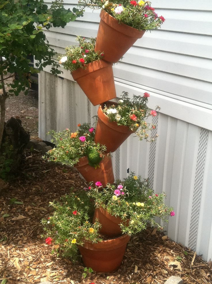 Tipsy Flower pots...easy to make. You will need 5-6 clay pots, one large pot for the bottom, 5' rebar (reinforcing steel rod) purchase from Lowes or Home Depot. Drive the rod in the ground about 2 foot. Put first clay pot on...go ahead add potting soil. Now add the next pot, angle to the side, add soil....continue until you stack all the clay pots. Enjoy!