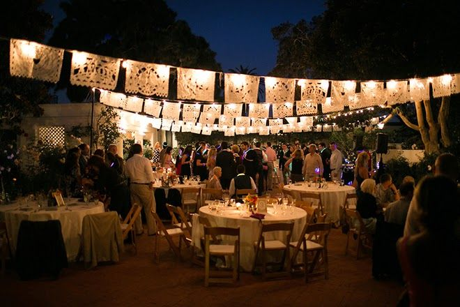 This Spanish themed wedding uses paper flags with string lights to set the tone for an evening wedding reception