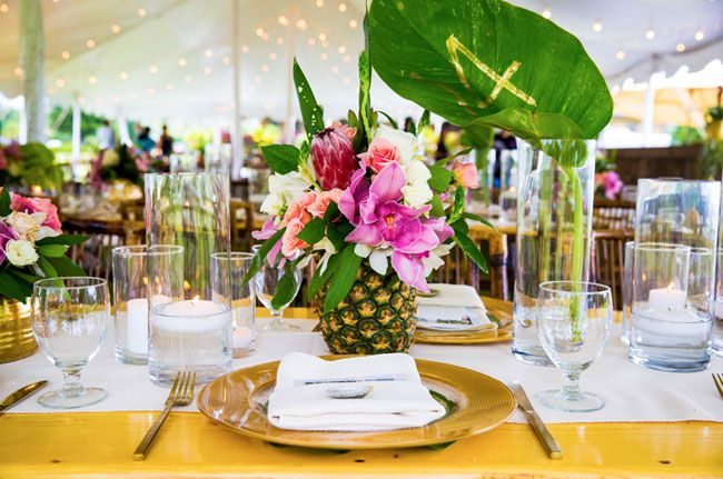 Golden Vessels, Tropical Foliage, Gold Rim Chargers, Bamboo Chairs, Pineapples Made into a Centerpiece.  Floral, Event Design and Decor Rentals - MartinRoberts Design Hawaii   info@martinroberts.com  Instagram/martinrobertsdesign  Coordinator : Moana Events