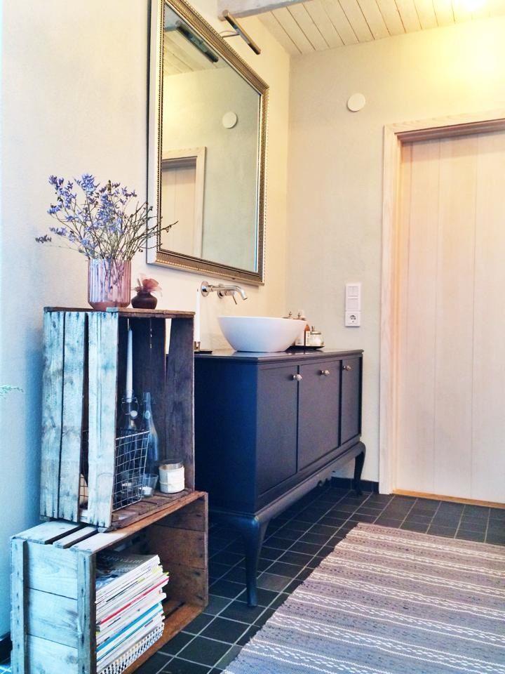En gammal tavelram med belysning, gamla äppellådor och ett skåp blir ett annorlunda badrum! Källa: Facebook / grupp Återbruka mera!