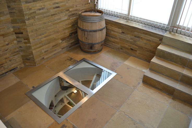 White Spiral Cellar with brown leather treads surrounded in perfect harmony by Mazeras African Sandstones