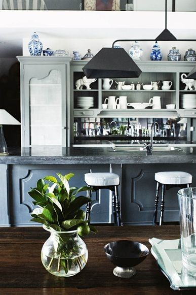 These are the most popular kitchens in Vogue Living: Classic French provincial style is achieved through the combination of this blue-grey island bench and an elegant collection of white and blue-and- white jugs, vases and china.