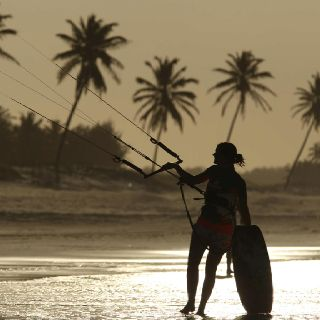Kite surfing girl silhouette with palm trees and beautiful light