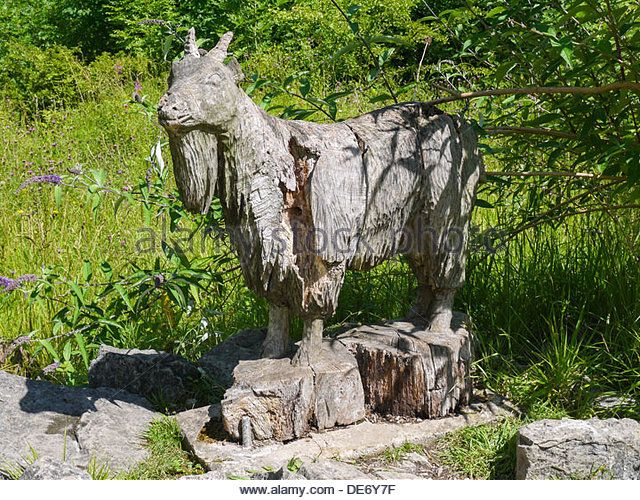 Wooden Carved Sculpture of a goat taken at the Crich Tramway Museum in Derbyshire, United Kingdom. - Stock Image