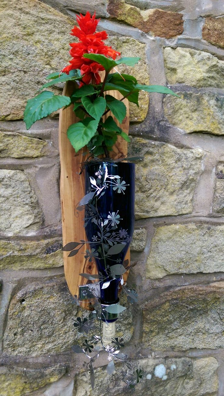 Wine bottle mounted onto olive wood and used as a planter.