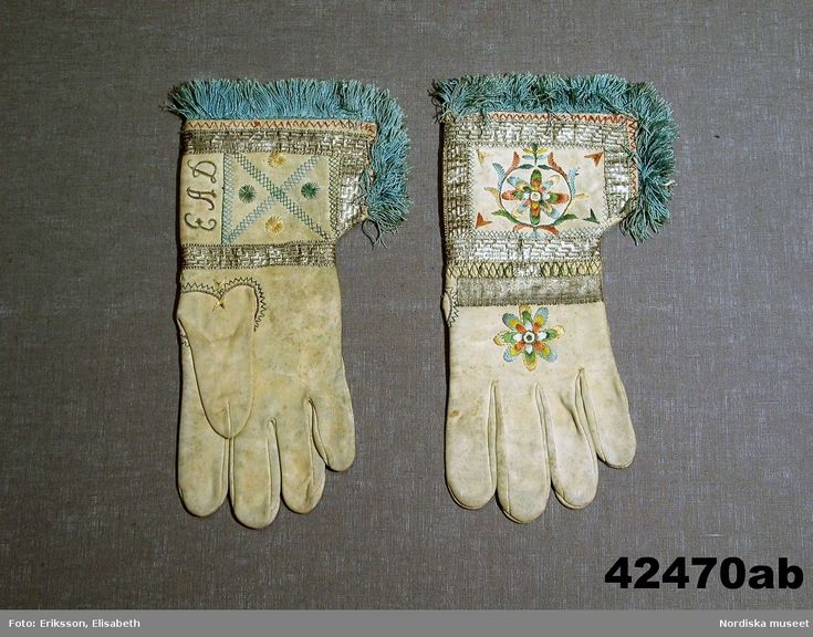 SE Östra Göinge. Ett par fingerhandskar av ljusgult sämskskinn med lång krage av 1600-talstyp med slits i sidan och kantad med ljusblå silkefrans samt påsydda silvergaloner .