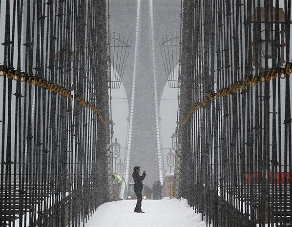 A man takes pictures from the Brooklyn Bridge during a snowstorm in New York. - Week in pictures: 15 March