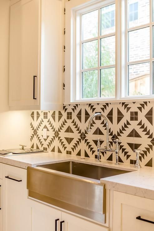 White and black Mediterranean kitchen boasts a window framed by Cement Tile Shop Tulum Tiles positioned above a stainless steel apron sink with a polished nickel deck mount faucet fixed to a honed white marble countertop accenting white shaker cabinets donning oil rubbed bronze hardware.
