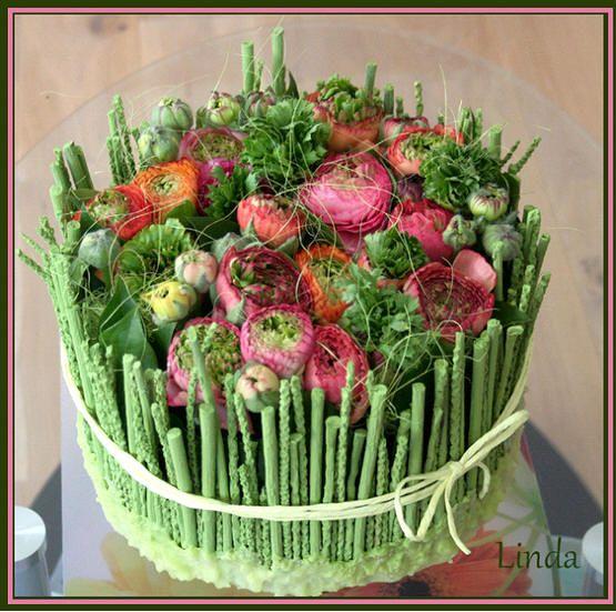 Taart met piep-en-steekschuim op elkaar, kaarsvet, takjes met lijm, blad met spelden, bloemen (ranonkels), sisal en raffia