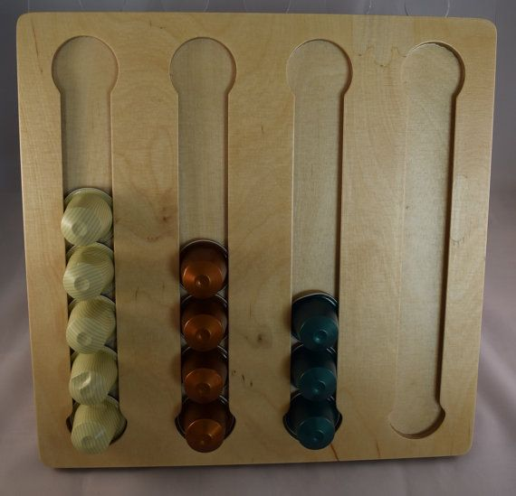 Práctico soporte cápsula de pared hecho de madera de hasta 60 (grande) o 28 cápsulas Nespresso (pequeños)  Fácil llenar del dispensador de cápsulas con una abertura redonda en la parte superior y el retiro a través de una abertura especial en la parte inferior de las ranuras  4 ranuras útiles para diferentes tipos de café 6 ranuras para la nespresso lage 60 capsul dispender  En el soporte para cápsulas de café está hecho de hojas multiplex de abedul de calidad en un CNC procesamiento centro…