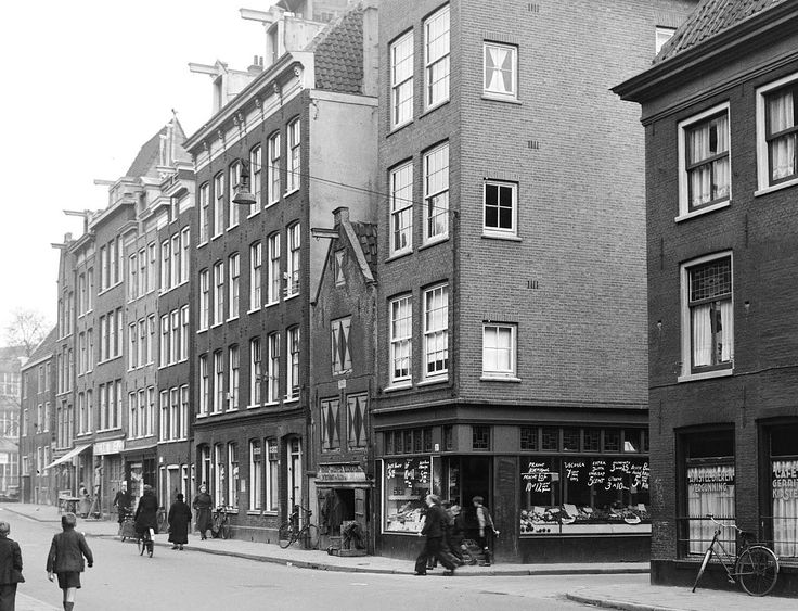 1941. A view of the Willemsstraat in the Jordaan neighborhood of Amsterdam seen from the Eerste Goudsbloemdwarsstraat towards the Brouwersgracht. Starting at the corner, from right to left, a vegetable store and a second-hand clothing store. Photo Stadsarchief Amsterdam. #amsterdam #1941 #Willemsstraat #Jordaan