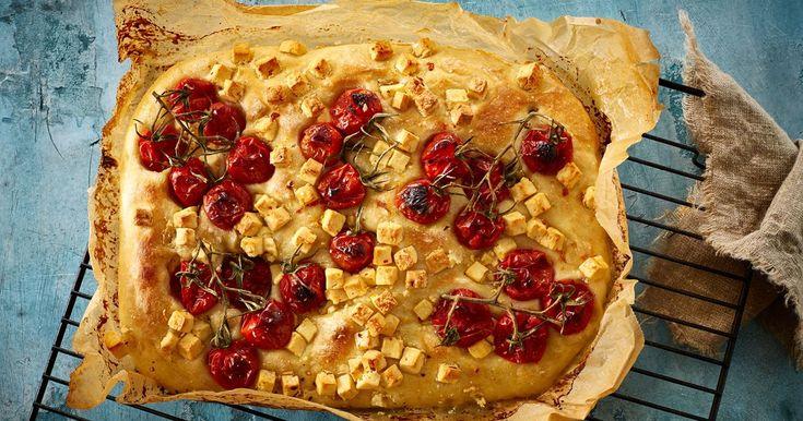 Focaccia er et fladbrød i familie med pizzaen. Her i en rustik version med smukke stilktomater og ost på toppen.