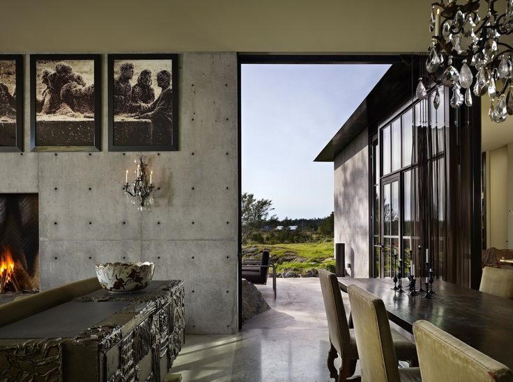 A large pivoting steel and glass door provides access to a terrace.
