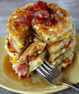 Bacon and Corn Griddle Cakes combine sweet and savory, topped with maple syrup.