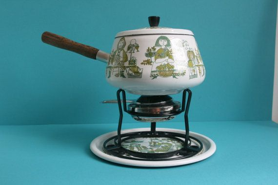 A vintage fondue pot with burner. This fondue set has the popular Turi Market decor, designed by Turi Gramstad Oliver, with lovely hand painted