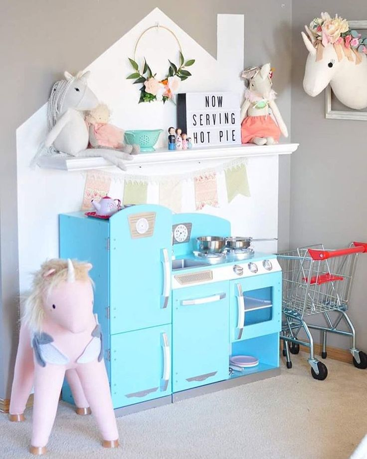 A house stenciled onto the wall of the playroom for a whimsical creative kitchen.  unicorn themed playroom. unisex children kitchen. felt flowers. land of nod unicorn. target pillowfort unicorn. dainty cheeks unicorn from anthropology. wooden peg doll family.