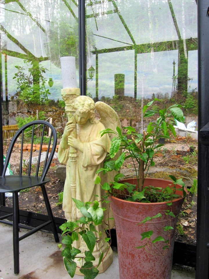A cherub with the function of a candelabre in my greenhouse. Old chairs from fleemarkets have been painted black and are used around the dining table.
