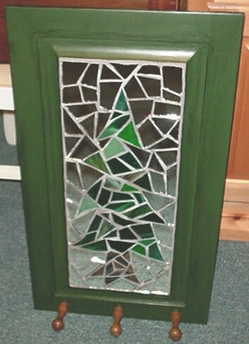 Old cabinet door redone with a mosaic sub tree with an initial...doing it.