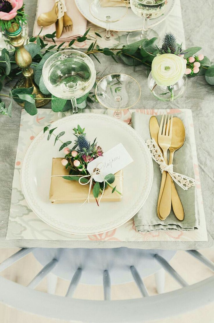 Patterned place mat, sage tablecloth and napkins, kraft paper package with floral sprigs, gold flatware and accessories