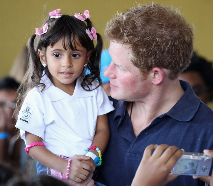 Prince Harry holds 3-year-old Mayara Pereira in Brazil.
