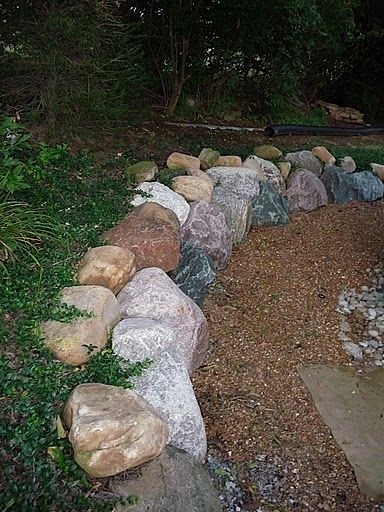 Boulder retaining wall behind our Amish gazebo...adds beautiful colors and texture to the landscaping! Architectural Landscape Design