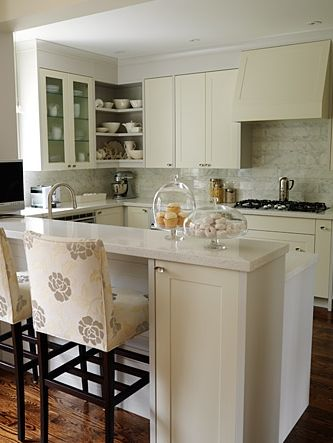 gorgeous ivory kitchen cabinets, marble tiles backsplash, caesarstone quartz counter tops and sarah Richardson custom upholstered barstools.  [paint tans] ICI Dulux French White
