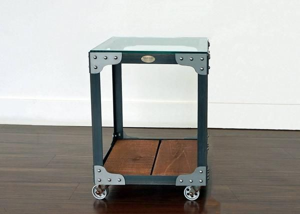 "Industrial End Table - Tannery Tool Trolley - Featuring a gloss clear coat steel finish, an oak wood shelf stain and a 3/8 inch clear glass table top. Made from steel angle iron, rough sawn white pine with a tempered glass table top.  Fastened with rivets and accent corner brackets, mounted on casters with a decorative vintage style brass boilerplate on front. 18"" W x 20 1/2"" D x 24"" H, 49 lbs. Duty Free."