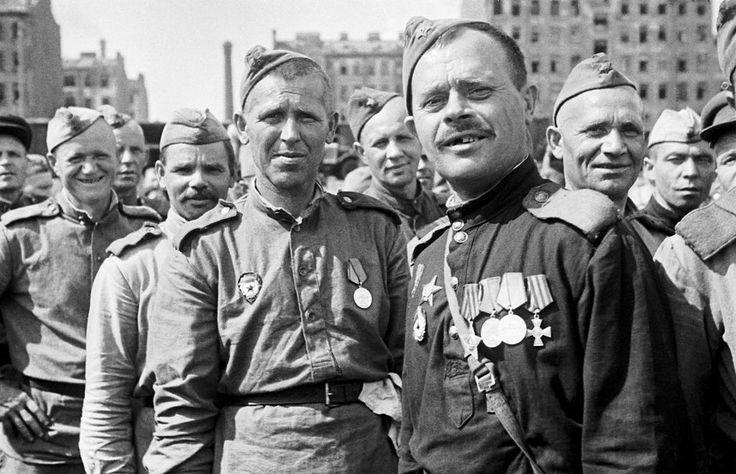 """June 1945: Demobilized Red Army troops return home from the front. The man nearest the camera, aside from missing half his front teeth, carries a cross decoration, obviously awarded to him by a """"capitalist"""" ally. This fact alone could have put him at risk of being """"observed"""" by the NKVD."""
