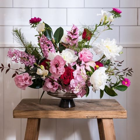 Here's a monochromatic, low dish arrangement using a mix of textures for a more natural, organic feel.   Mix of peonies, lisianthus, hyacinth and other lovelies.