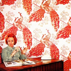 Florence Broadhurst in front of 'Peacock' wallpaper