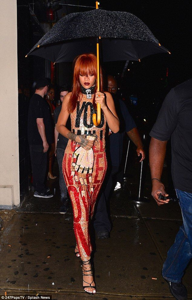 Keeping dry: Rihanna sheltered under a giant umbrella as she headed for a night out in the rain in NYC on Sunday