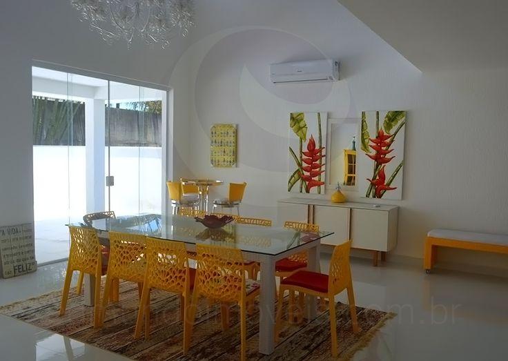 Ao redor da mesa retangular em madeira e vidro, dez cadeiras Gruvyer amarelas compõem a sala de jantar. Tons fortes de amarelo e vermelho também foram os escolhidos para o pufe lateral e os bancos altos na mesa bistrô que completam o ambiente.