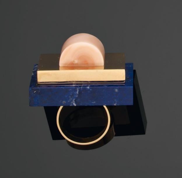 ETTORE SOTTSASS -   Rare bague en or, lapis-lazuli et corail. 1984/1986 Réalisée par Cleto Munari. Signée Sottsass, Cleto Munari et poinçonnée. Très peu d'exemplaires connus. Tdd: 55. H_2,7 cm L_3,8 cm Bibliographie: La bague est illustrée à la page 147 du livre « Cleto Munari, Dandy Design » E. Biffi Gentile, éd. Electa, Napoli, 1997. (estimé entre 4500 et 5500 €)