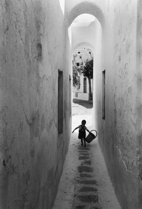 GREECE. The Cyclades Archipelago. Santorini island, 1951. [Boy holding a basket, walking down a white wall corridor, Greece]. Copyright © David Seymour/Magnum Photos