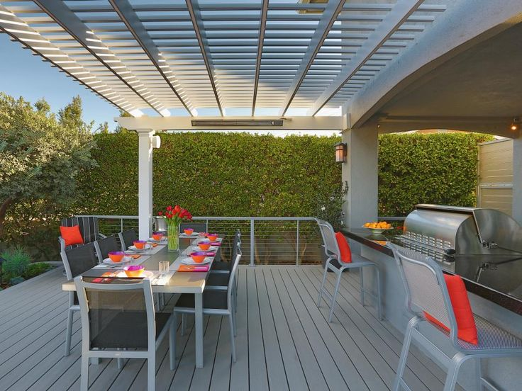A white pergola lets sunlight sneak through to illuminate the long, contemporary dining table with bright, summery table settings. Bold orange accents pop against the industrial furniture and neutral floor. A grill is surrounded with counter space for additional seating or prepping.