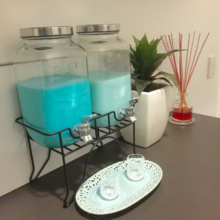 Kmart dual drink dispensers used for laundry detergent and fabric softener. Chantilly platter with crystal shot glasses as dispensing cups. Styled with Kmart plant and scented reeds from Dusk.