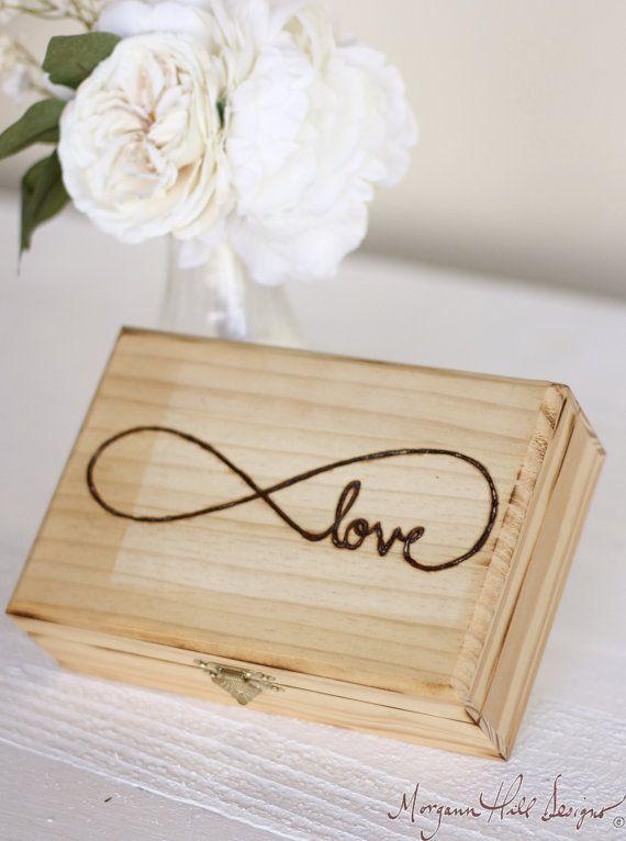 Una caja rústica para los anillos de bodas, en la tapa tiene grabado la palabra amor con el símbolo de infinito integrado.