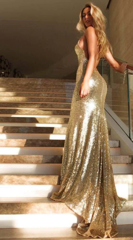 Gold goddess dress from Studio Minc. The goddess is one of our classic fishtail silhouettes. This simple backless gown speaks for itself. This gown has a very low open back and a V neck line with thin stretch straps. This dress is timeless and the sequin falls like glistening liquid. However, this Gold Goddess has taken glamour to new heights with an extremely gorgeous train.  Classic fishtail silhouette
