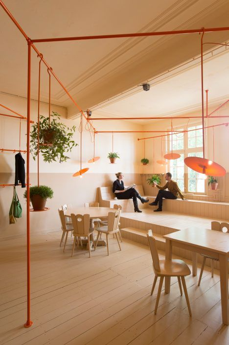 Dutch design studio Overtreders W has used a bold colour palette and an elaborate pipe network to give a concert-hall cafe a cheap but cheerful makeover.