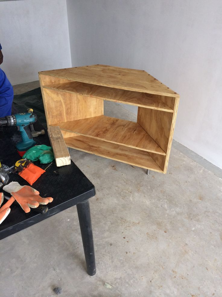Corner tv unit built from reclaimed plywood from a construction site.