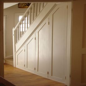 Put paneling on the side of the stairs with the lower panels being hidden doors so you can access plumbing for under stairs bathroom fixtures.