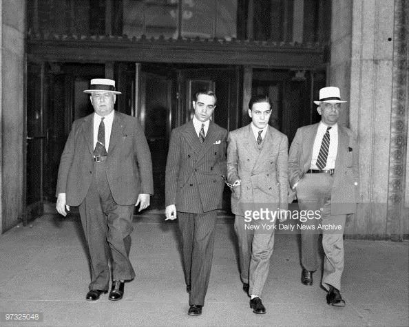 Handcuffed together are Lucchese mobsters James Plumeri aka Jimmy Doyle and Johnny Dioguardi aka Johnny Dio as they leave court after session. There is nothing delicate about Racketeer Plumeri who is on trial for conducting a trucking shakedown that earned him a small fortune. (1937)